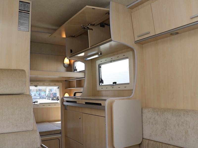 白を基調とした車内。中央にキッチンと冷蔵庫があります